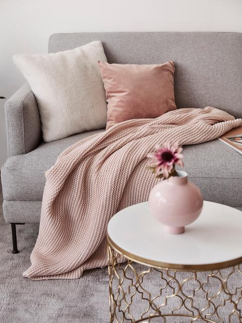 Szara kanapa z poduszkami oraz kocem w kolorze millenial pink w salonie z białym stolikiem