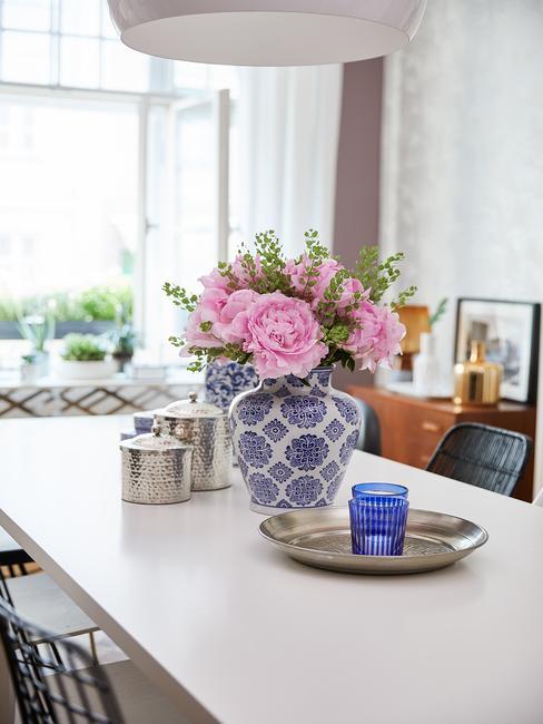 Niebieski, porcelanowy wazon z różmai postawiony na blacie stołu obok misy dekoracyjnej oraz srebrnych naczyń