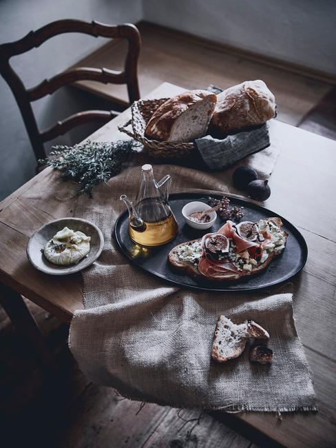 Fragment kuchni w stylu prowansalskim z nakrytym jedzeniem drewnianym stołem