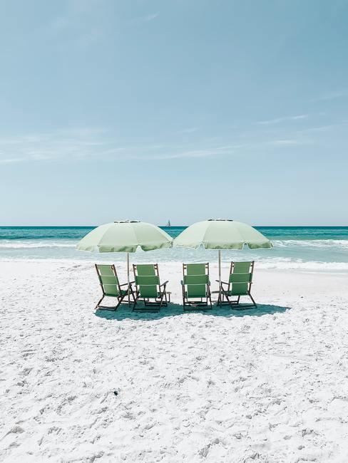 Cztery zielone leżaki oraz dwa parasole rozstawione na pustej plaży