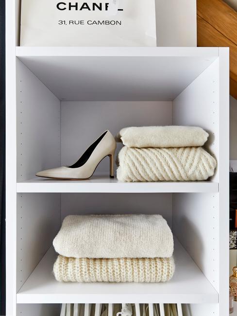 Kremowe swetry, równo poukłade w szafie, obik jasne szpilki