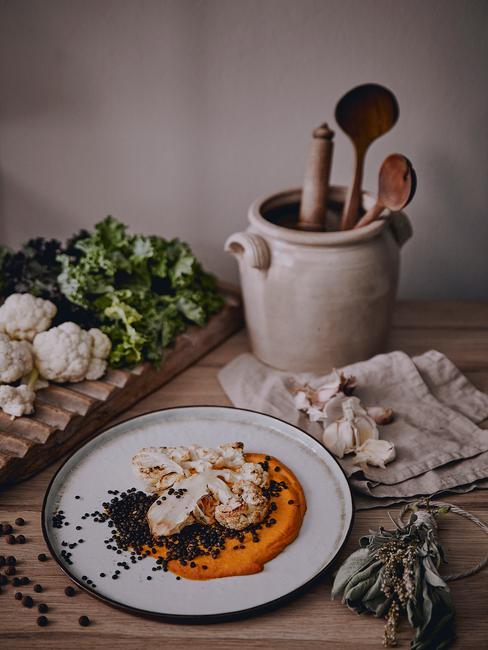 Biały talerz w kuchni z drewnianym blatem, obok ceramicznego dzbanka z drewnianymi łyżkami oraz warzywami na desce