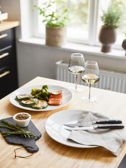 Wyspa w kuchni z drewnianym blatem, dwoma kieliszkami do wina oraz dwoma talerzami