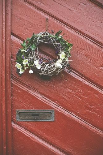 Wieniec na drzwi zrobiony z gałązek, liśmy oraz świeżych kwiatów