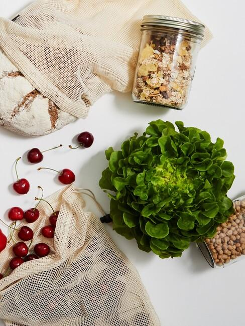 Biały blat z ekologicznymi torebkami na zakupy, ziarna umieszczone w szklanych słoikach oraz sałata