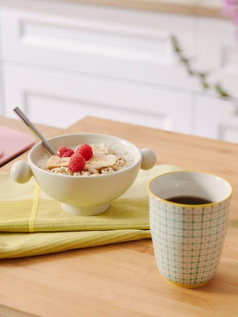 Drewniany blat z białą miseczką z owsianką na żółtej ściereczce i zółty kubek z kawą