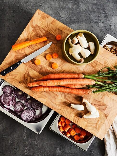 Drewniana deska z nożem, pokrojoną marchewką oraz metalowymi pojemnikami z papryką i czerwoną cebulą
