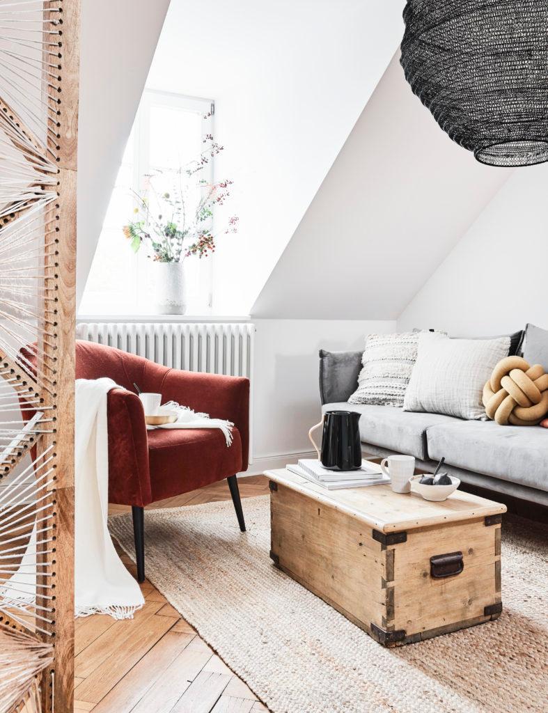 Salon w stylu skandynawskim z szara kanapą, czerwonym fotelem i drewnianą skrzynią jako stolik kawowy