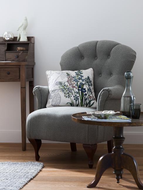 Salon w stylu country w ciemnych odcieniach z szarym fotelem oraz drewnianym sekretarzykiem