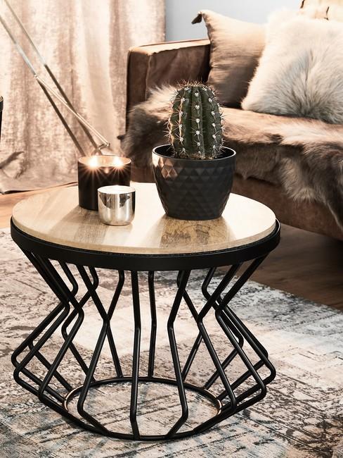 Zbliżenie na drewniany stolik kawowy z czarnymi, metalowymi nogami w salonie w stylu industrialnym