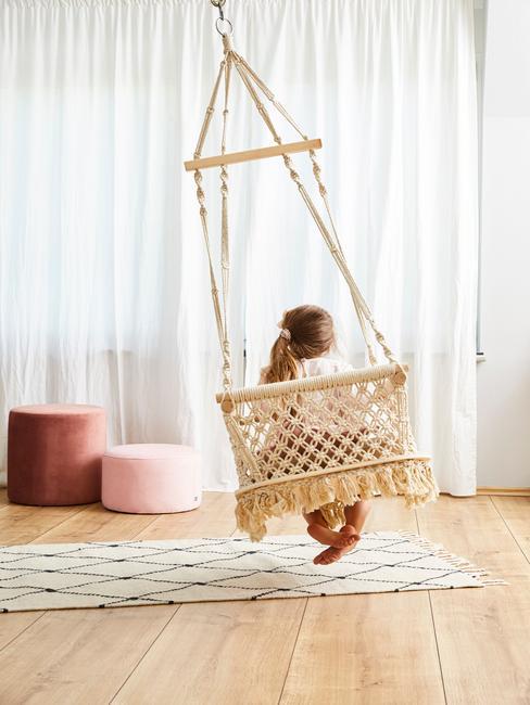 Dziewczyna siedząca na hamako-huśtawce w saonie z dywanem oraz dwoma pufami