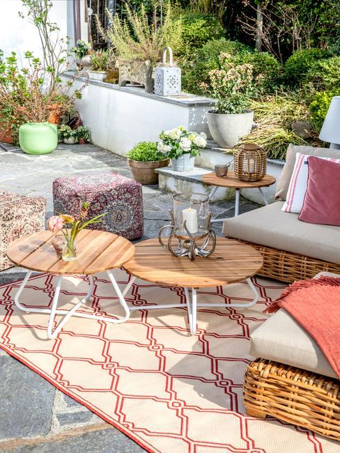Strefa relaksua składająca się ze stolików oraz krzeseł w małym ogrodzie