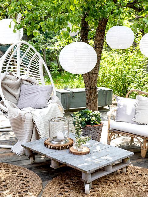 Fragment ogrodu z białą huśtawką, rattanowym krzesłem oraz stolikiem z europalety