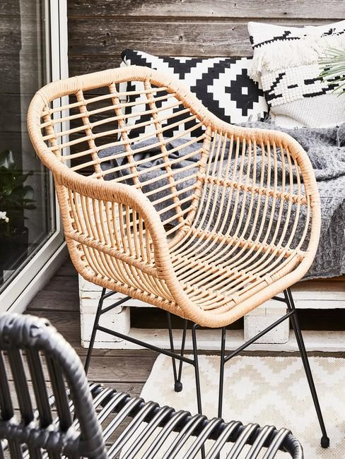 Zlbiżenie na plecione krzesło, za któym stoi sofa zrobiona z palety
