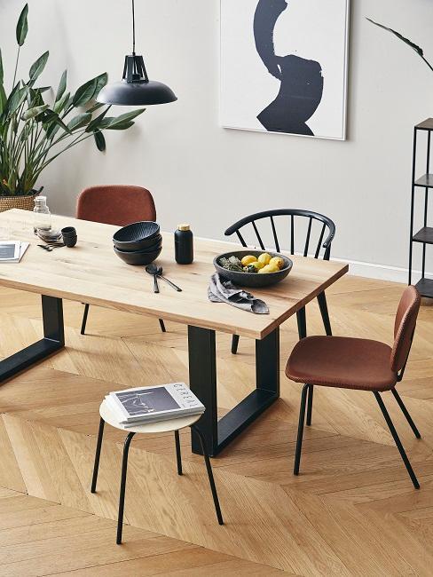Jadalnia w stylu minimalistycznym z drewnianym stołem oraz różnymi krzesłami i dekoracjami w pomieszczeniu