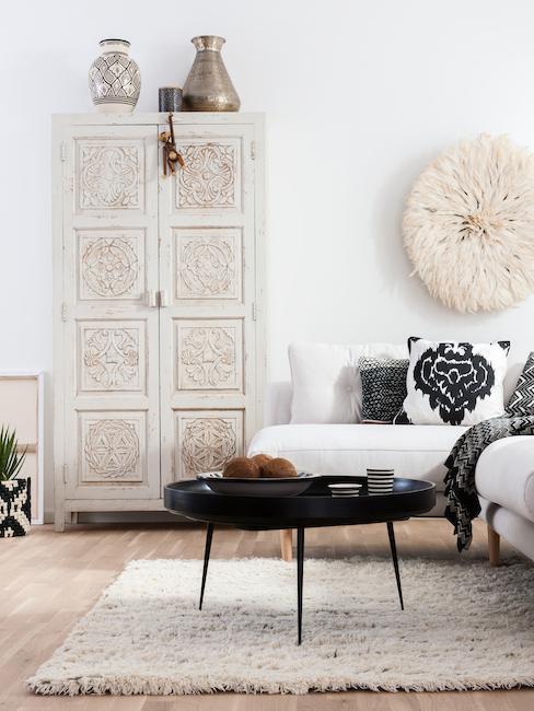 Salon boho z omodą we wzory, biała kanapą oraz czarnymi dekoracjami w postaci stolika oraz poduszek