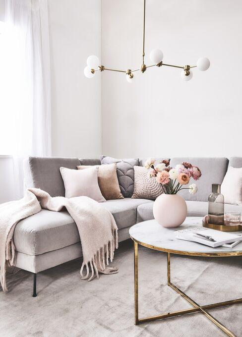 Salon z szarą sofą z poduchami, marmurowym stolikiem i wyrazistym akcentem w postaci lampy
