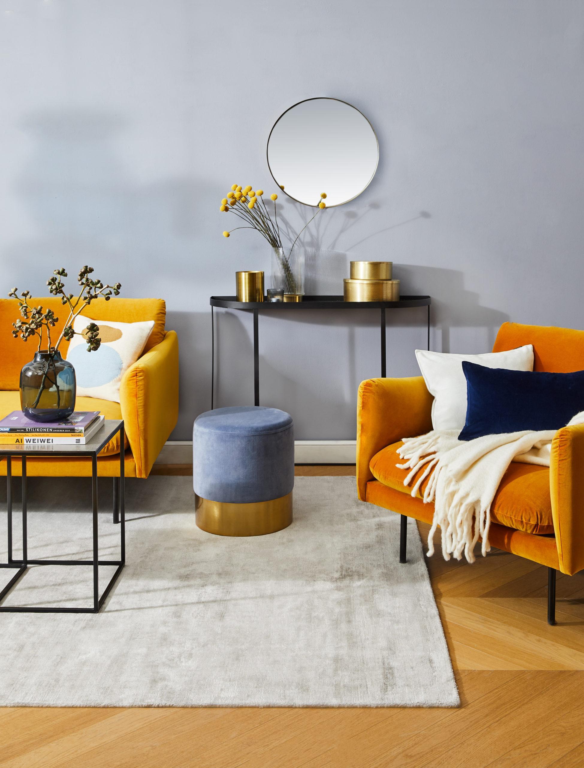 Salon z pomarańczową sofą, czarnym stolikiem oraz błękitną ścianą