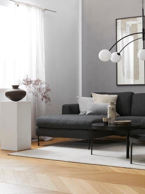 Salon z sofą w szarej barwie, białą kolumną z wazonem oraz stojąca lampą