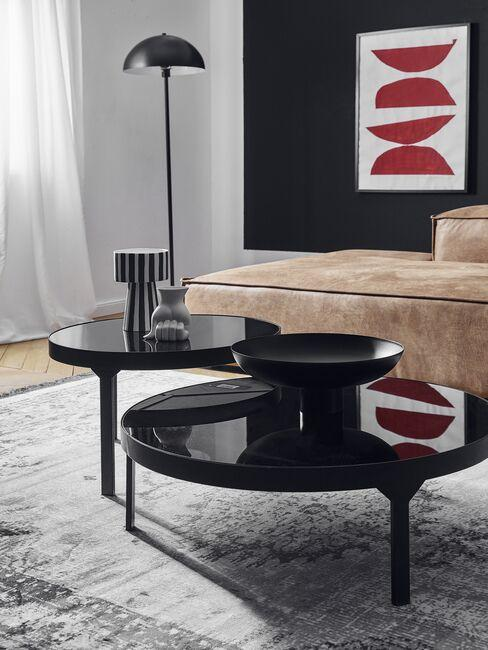 Czarne stoliki kawowe przy jasnej sofie na tle ciemnej ściany z designerską grafiką