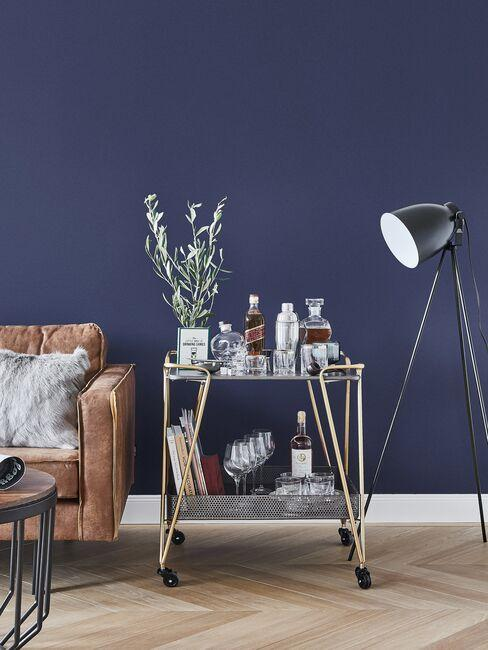 Złoty barek obok skórzanej kanapy i industrialnej lampy w salonie z granatową ścianą