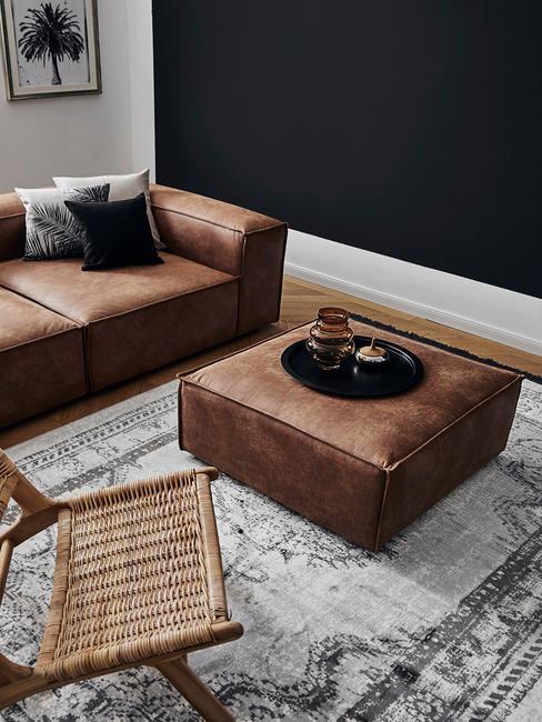 Salon ze skórzaną sofą, pufem, rattanowym krzesłem oraz ścianami w kolorze bieli i ciemnego granatu