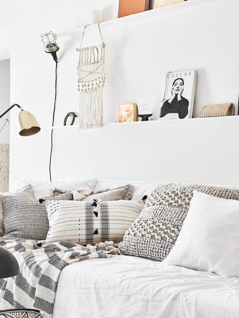 Salon boho w białą ścianą, sofą oraz szarymi dodatkami