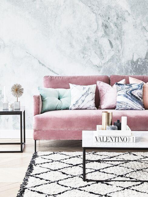 Subtelny, kobiecy salon z różową sofą i tapetą z motywem imitującym marmur