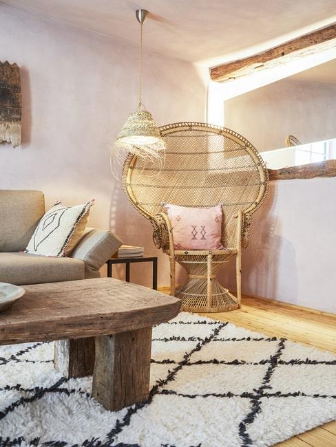 Pleciony fotel i drewniany stół w salonie boho
