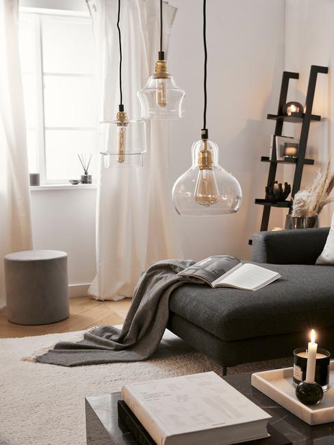 Salon z szarą sofą, czarną półką, pufem oraz nowoczesnymi wiszącymi lampami w salonie
