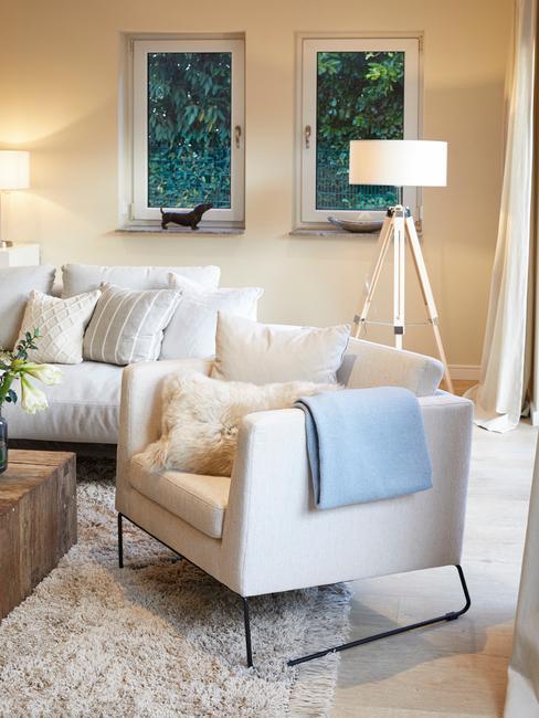 Jasny salon z białą sofą i fotelem, poduszkami, drewnianym stolikiem oraz lampą