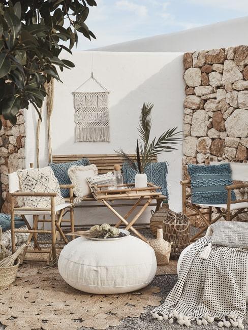 Taras w stylu śródziemnomorskim z meblami z bambusa, białym pufem oraz dekoracjami