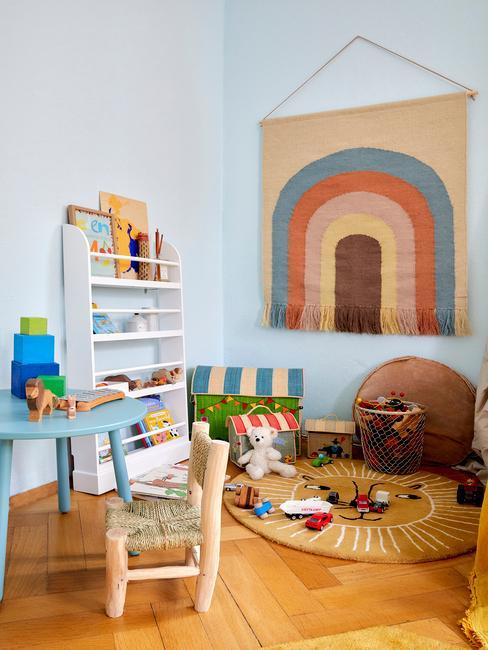 Niebieski pokój z obrazkiem na ścianie, białą półką na zabawki, stoliczkiem, krzesełkiem i dywanem