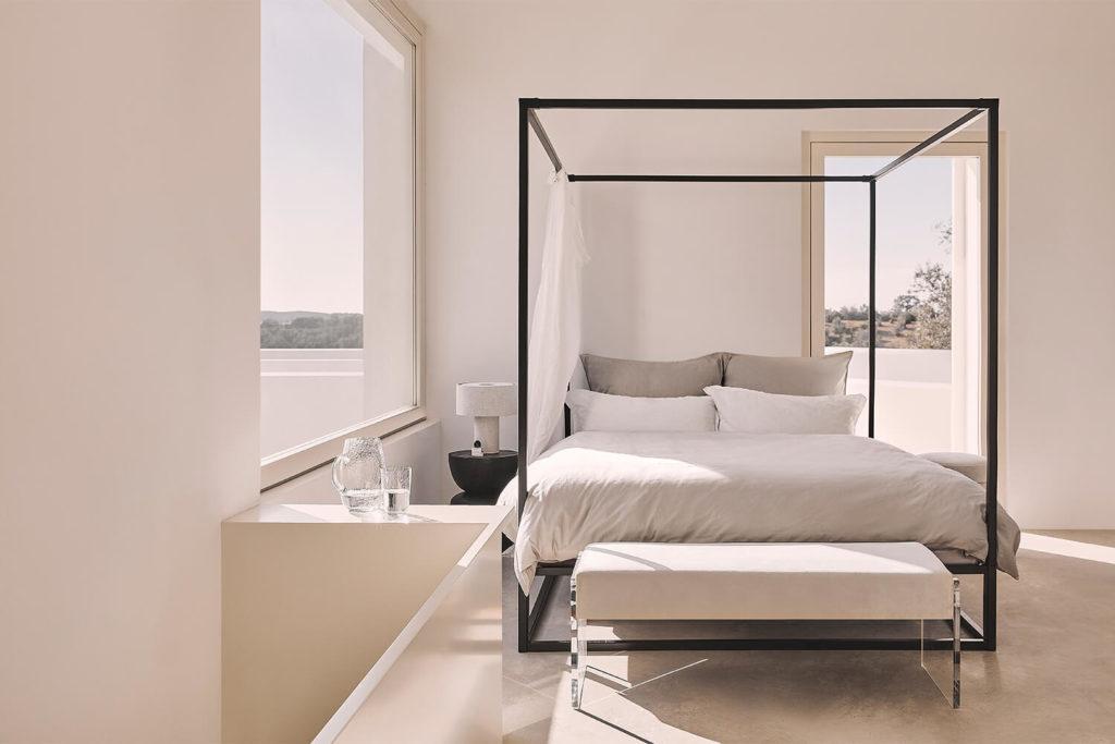 Jasna sypialnia z dużym łóżkiem z baldachimem, białym stolikiem