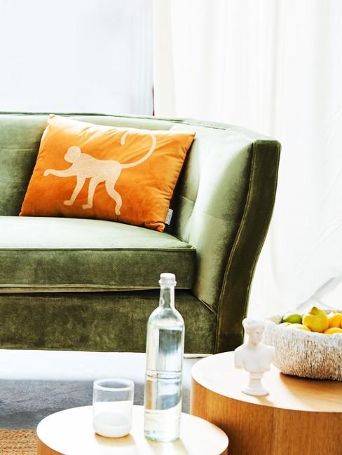 Sofa w kolorze oliwkowym z pomarańczową poduszką oraz drewnianymi stolikami