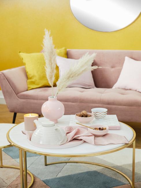 Fragment salonu z żółtą ścianą oraz sofą w kolorze brudnego różu