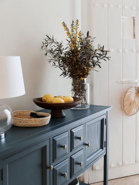 Fragment przedpokoju w białym kolorze i niebieską komodą z lampą oraz wazonem kwiatów