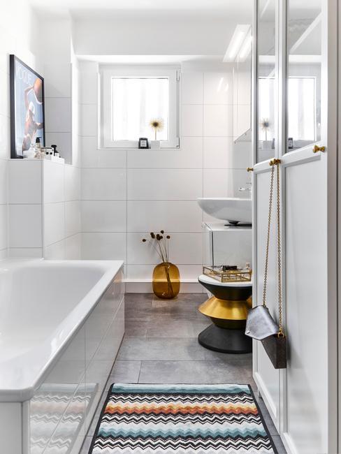 Biała łazienka z szarą podłogą i wzorzystym dywanem