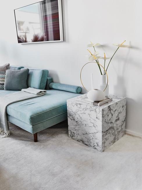 Jasny salon z turkusową kanapą oraz marmurowym stolikiem pomocniczym