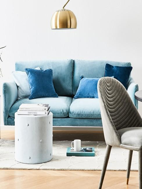 Biały salon z szarym krzeslem, sofą oraz białym stolikiem oraz złotą lampą