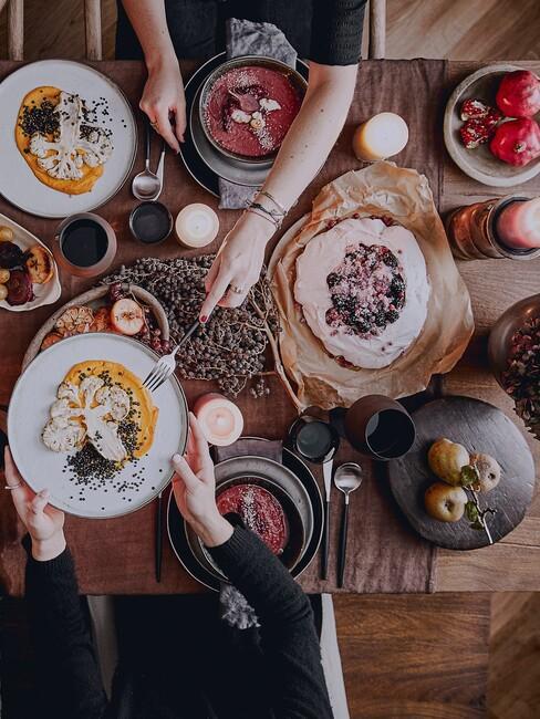 Zastawiony, drewniany stół z jedzeniem przy którym siedzą osoby