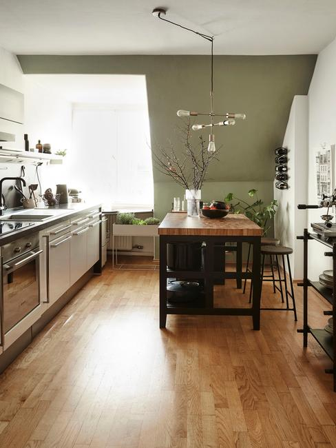 Kuchnia na poddaszu z białymi meblami, drewnianym stołem oraz jedną, oliwkową ścianą