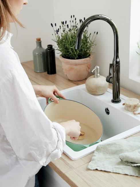 Kobieta stojąca przy dużym zlewie i myjąca garnek żeliwny w zielonym kolorze