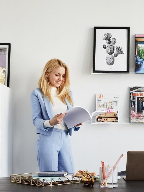 Kobieta stojąca w białym biurze i przeglądająca magazyn wnętrzarski
