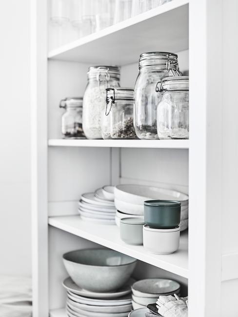 Zl=bliżenie na białą półkę z zastawą kuchenną i szklanymi pojemnikami