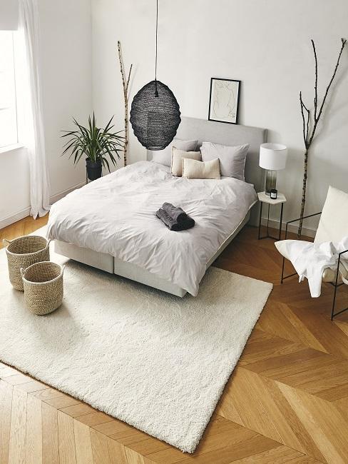 Sypialnia w stylu boho z dużym łożkiem, białym dywanem, koszami rattanowymi oraz roślinami