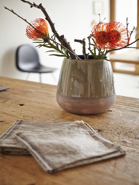 Drewniany, rustykalny stół kuchni z ceramicznym wazonem z kwiatami oraz lnianymi podkładkami