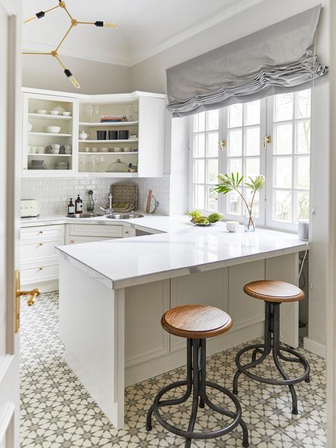 Elegancka, biała kuchnia z marmurowym blatem, małym stołem barowym oraz wiszącymi półkami