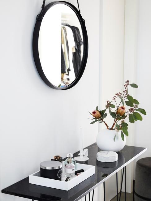 biały przedpokój z lustrem o czarnej ramie oraz półce z dekoracjami
