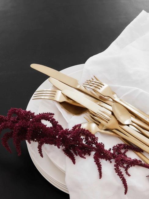 Czarny stół z białą zastawą, złotymi sztućcami oraz fioletową gałązką